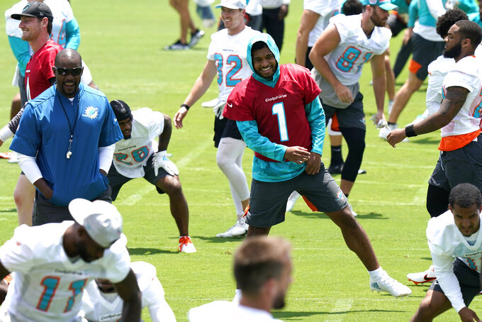 Miami Dolphins quarterback Tua Tagovailoa (1) stretches at the team's NFL football training facility, Wednesday, May 26, 2021, in Davie, Fla. At left is head coach Brian Flores. (AP Photo/Lynne Sladky)