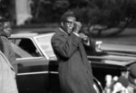 FILE - In this Nov. 4, 1974, file photo, Robert Mugabe takes part in the Rhodesia conference in Geneva, jokingly puts up his fists as he encounters newsmen. Mugabe, the longtime leader of Zimbabwe who was forced to resign in 2017 after a military takeover, has died at 95. (AP Photo, file)