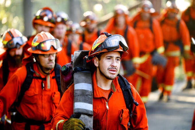 FILE - In this Oct. 29, 2019, file photo, inmate firefighters prepare to battle the Kincade Fire near Healdsburg, Calif. Despite pandemic restrictions, the California legislature managed to pass hundreds of bills in 2020, including one that would allow former inmate firefighters to quickly apply to have their criminal records expunged after their release, which gives them a shot at becoming professional firefighters or seeking employment in other licensed professions. (AP Photo/Noah Berger, File)
