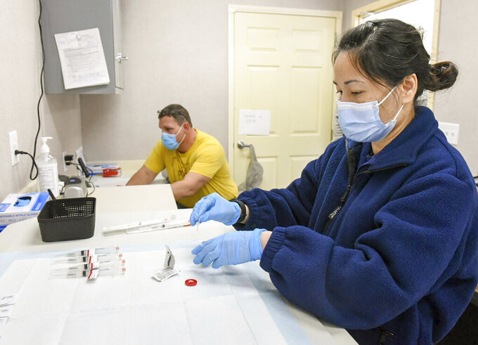 Quynh Tran, a clinical pharmacist from The Public Health Commission Corps, prepares a vial of Moderna vaccine on Tuesday, April 13, 2021, at a mobile vaccination unit currently stationed at the Oxford Casino, in Oxford, Maine. The clinic pivoted to administering the Moderna vaccine after the Johnson & Johnson vaccines were paused with guidance from the Center for Disease Control. (Andree Kehn/Sun Journal via AP)