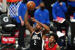 Los Angeles Clippers forward Kawhi Leonard, left, shoots as Houston Rockets guard Kevin Porter Jr. watches during the first half of an NBA basketball game Friday, April 9, 2021, in Los Angeles. (AP Photo/Mark J. Terrill)