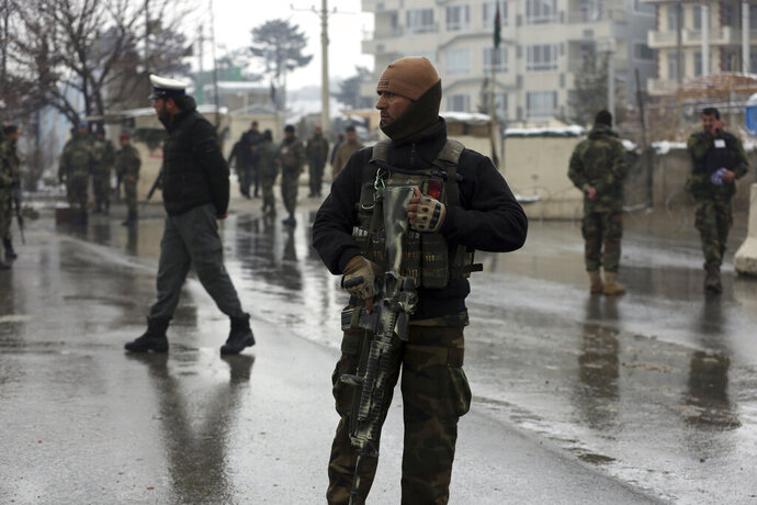 FILE- in this Feb. 11, 2020, photo, national army soldiers stand guard at the site of suicide attack near the military academy in Kabul, Afghanistan, A United Nations report says Afghanistan passed a grim milestone with more than 100,000 civilians killed or hurt in the last 10 years since the international body began documenting casualties in a war that has raged for 18 years. (AP Photo/Rahmat Gul, file)