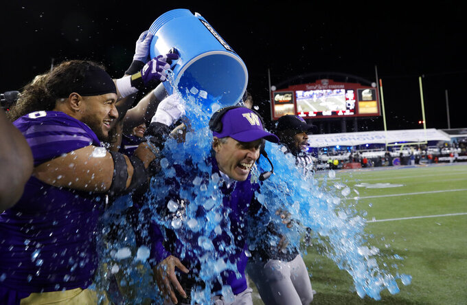 Washington head coach Chris Petersen is doused at the Las Vegas Bowl NCAA college football game against Boise State at Sam Boyd Stadium, Saturday, Dec. 21, 2019, in Las Vegas. Washington beat Boise State 38-7. (AP Photo/Steve Marcus)