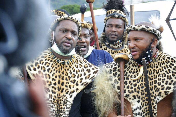 """Prince Misuzulu Zulu, left, flanked by fellow warriors in traditional dress at the KwaKhangelamankengane Royal Palace, during a ceremony, in Nongoma, Friday May 7, 2021. A new Zulu king in South Africa has been named amid scenes of chaos as other members of the royal family questioned Prince Misuzulu Zulu's claim to the title. He was suddenly whisked away from the public announcement at a palace by bodyguards. The controversy over the next king has arisen after the death in March of King Goodwill Zwelithini, who had reigned since 1968. Zwelithini apparently named one of his six wives, Queen Mantfombi Shiyiwe Dlamini Zulu, as the """"regent of the Zulu kingdom"""" in his will. But her death just over a week ago after holding the title for only a month has thrown the royal succession into turmoil. (AP Photo)"""