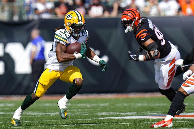 Green Bay Packers running back Aaron Jones (33) cuts away from Cincinnati Bengals defensive end Sam Hubbard (94) in the first half of an NFL football game in Cincinnati, Sunday, Oct. 10, 2021. (AP Photo/AJ Mast)