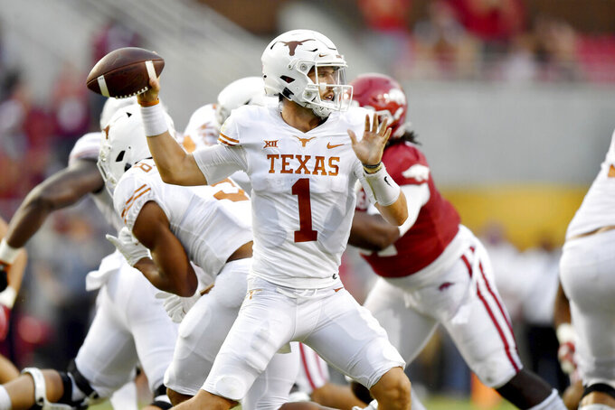 Texas quarterback Hudson Card (1) drops back to pass against Arkansas during the first half of an NCAA college football game Saturday, Sept. 11, 2021, in Fayetteville, Ark. (AP Photo/Michael Woods)