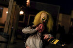 An cast member dressed as a clown grabs and drags away a visitor of Terror Town, Saturday, Oct. 17, 2020, in Williamsburg, Ohio. In a year when fear and death have commandeered front-row seats in American life, what does it mean to encounter Halloween, a holiday whose very existence hinges on turning fear and death into entertainment? (AP Photo/Aaron Doster)