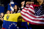 Members of the audience wave Venezuelan and American flags as President Donald Trump speaks to a Venezuelan American community at Florida Ocean Bank Convocation Center at Florida International University in Miami, Fla., Monday, Feb. 18, 2019, to speak out against President Nicolas Maduro's government and its socialist policies. (AP Photo/Andrew Harnik)