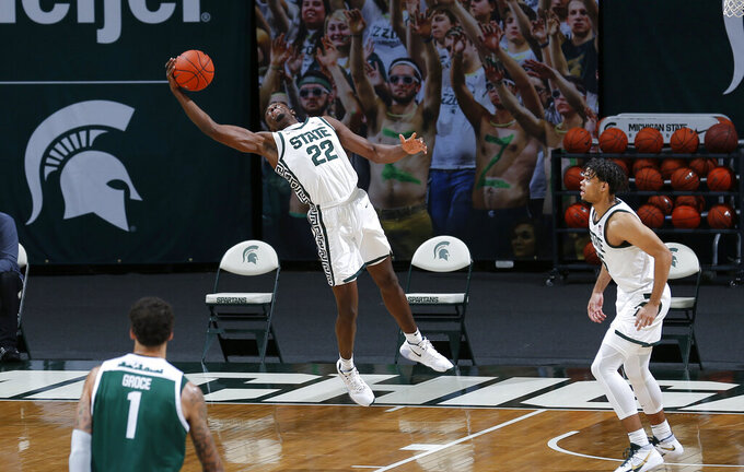 Michigan State's Mady Sissoko (22) leaps for a rebound as Eastern Michigan's Ty Groce (1) and Michigan State's Malik Hall, right, watch during the second half of an NCAA college basketball game Wednesday, Nov. 25, 2020, in East Lansing, Mich. Michigan State won 83-67. (AP Photo/Al Goldis)