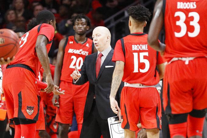 Cincinnati head coach Mick Cronin, center, directs his players in the first half of an NCAA college basketball game against Houston, Sunday, March 10, 2019, in Cincinnati. (AP Photo/John Minchillo)