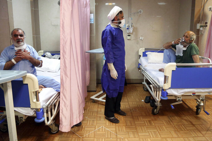 In this Saturday, March 7, 2020, a cleric talks with a patient infected with the new coronavirus, at a hospital in Qom, 78 miles (125 kilometers) south of the capital Tehran, Iran. With the approaching Persian New Year, known as Nowruz, officials kept up pressure on people not to travel and to stay home. Health Ministry spokesman Kianoush Jahanpour, who gave Iran's new casualty figures Sunday, reiterated that people should not even attend funerals. (Mohammad Ali Marizad/Rasa News Agency via AP)