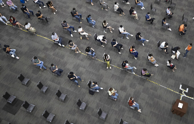 Airline employees rest after receiving the Sinovac COVID-19 vaccine to be sure there are not any side effects at the Siam Paragon shopping mall in Bangkok, Thailand, Tuesday, May 25, 2021. (AP Photo/Sakchai Lalit)