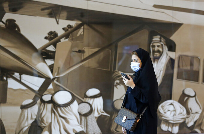 A Saudi passenger walks in front of an enlargement of an old photograph showing the late King Abdul Aziz Al Saud as he peers out of an airplane, at King Abdulaziz International Airport in Jiddah, Saudi Arabia, Monday, May 17, 2021. Vaccinated Saudis will be allowed to leave the kingdom for the first time in more than a year as the country eases a ban on international travel that had been in place to try and contain the spread of the coronavirus and its new variants. (AP Photo/Amr Nabil)