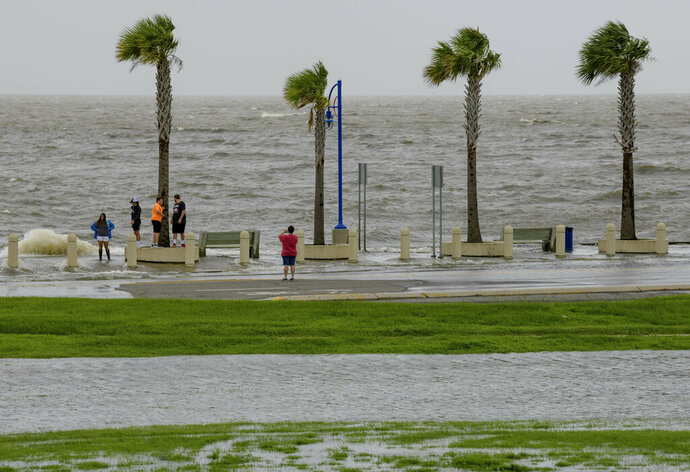 People check out the waves on Lakeshore Drive in New Orleans, La., Friday, July 12, 2019, as water moves in from Lake Pontchartrain from the storm surge from Tropical Storm Barry in the Gulf of Mexico. The area is behind a levee that protects the rest of the city. (AP Photo/Matthew Hinton)
