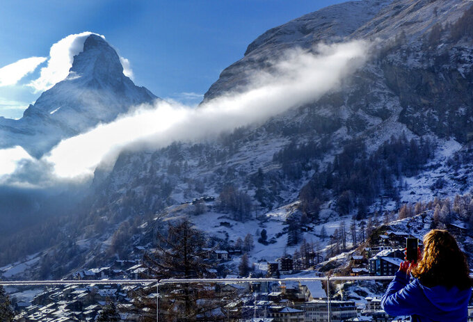 A woman takes a picture the Matterhorn, left, in Zermatt, Switzerland, Wednesday, Dec.2, 2020. Zermatt is home to one of the Swiss ski stations that has become an epicenter of discord among Alpine neighbors. EU member states Austria, France, Germany and Italy are shutting or severely restricting access to the slopes this holiday season amid COVID-19 concerns, Switzerland is not. (AP Photo/Jamey Keaten)