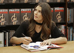 Danica Patrick talks to a fan as she autographs her new book during a book signing in Charlotte, N.C., Thursday, Jan. 4, 2018. The transition from race car driver to businesswoman was swift, and Patrick is now adjusting to a new celebrity life that doesn't include driving cars. (AP Photo/Chuck Burton)