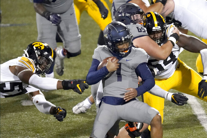 Illinois quarterback Isaiah Williams (1) escapes the grasp of Iowa defensive lineman Chauncey Golston during the second half of an NCAA college football game Saturday, Dec. 5, 2020, in Champaign, Ill. (AP Photo/Charles Rex Arbogast)