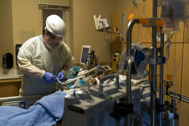 FILE - In this Nov. 19, 2020, file photo, respiratory care practitioner Scott Hoagland checks on a COVID-19 patient at Providence Holy Cross Medical Center in the Mission Hills section of Los Angeles. California's hospitals are being overwhelmed by a surge of coronavirus patients and some say the worst is yet to come. (AP Photo/Jae C. Hong, File)