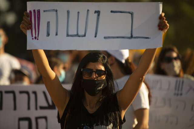 An Israeli social worker holds a sign in Hebrew that reads,