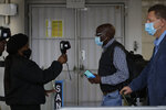 FILE — In this Thursday, Oct. 1, 2020 file photo passengers have their temperatures taken at the International O.R. Tambo Airport in Johannesburg, South African Health Minister, Zwerli Mkhize announced Monday, Oct. 19 2020 that he and his wife have tested positive for COVID-19, warning of a possible resurgence of the disease in the country. (AP Photo/Themba Hadebe/File)