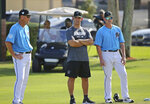 Miami Marlins Triple-A catching coordinator Jaime Quirk, and Marlins catching coach Brian Schneider, right, talk with Marlins Special advisor to baseball operations Jorge Posada during a workout at the team's spring training baseball facility in Jupiter, Fla., Monday, Feb. 18, 2019, (David Santiago/Miami Herald via AP)