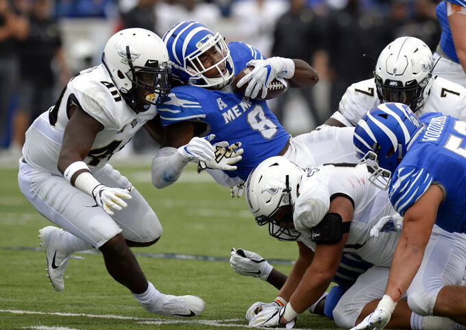 Memphis running back Darrell Henderson (8) runs for a first down as he is hit by Central Florida linebacker Eriq Gilyard (40) during the first half of an NCAA college football game Saturday, Oct. 13, 2018, in Memphis, Tenn. (AP Photo/Mark Zaleski)