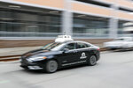 In this Jan. 4, 2019, photo made with a slow shutter speed, one of the test vehicles from Argo AI, Ford's autonomous vehicle unit, navigates through the strip district near the company offices in Pittsburgh. The people developing self-driving vehicles say it could be anywhere from 10 years to decades before the cars will be carrying passengers in every city. Researchers are trying to conquer a number of obstacles. (AP Photo/Keith Srakocic)