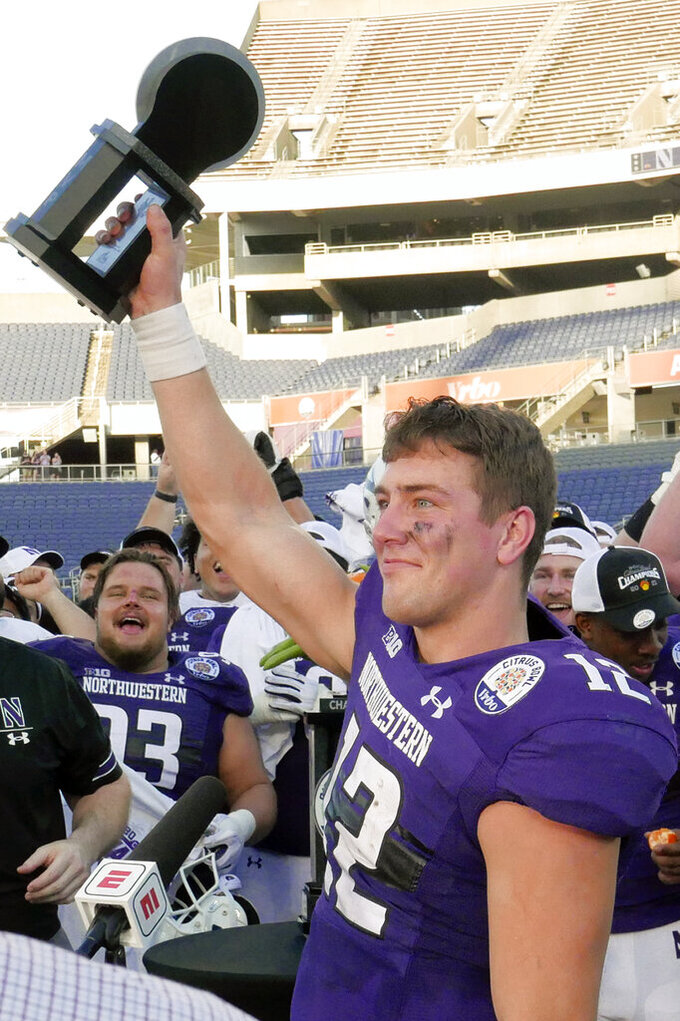Northwestern quarterback Peyton Ramsey holds his MVP trophy after winning the Citrus Bowl NCAA college football game against Auburn, Friday, Jan. 1, 2021, in Orlando, Fla. (AP Photo/John Raoux)