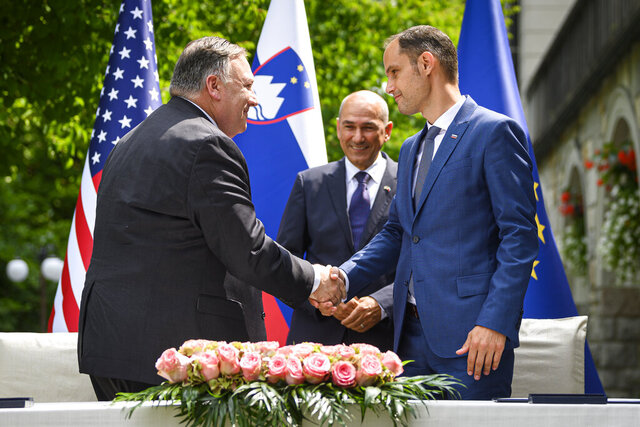 US Secretary of State Mike Pompeo, left, and Slovenia's Foreign Minister Anze Logar shake hands after signing an agreement on fifth-generation internet technology as Slovenia's Prime Minister Janez Jansa stands at center, in Bled, Slovenia, Thursday, Aug. 13, 2020. Pompeo is on a five-day visit to central Europe with a hefty agenda including China's role in 5G network construction. (Jure Makovec/Pool Photo via AP)