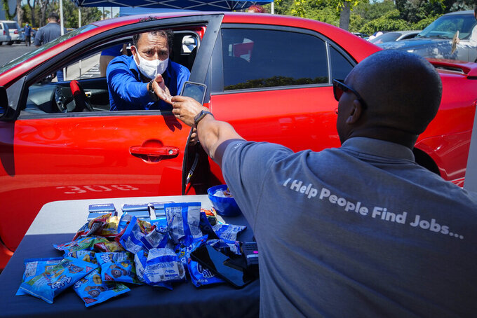 FILE - In this May 6, 2020, file photo, Brandon Earl, right, helps David Lenus, a job seeker, fill out an application at a drive up job fair for Allied Universal during the coronavirus pandemic, in Gardena, Calif. Coronavirus restrictions in California have put millions of people out of work, increasing the state's unemployment rate earlier this year to levels not seen since the Great Depression. (AP Photo/Chris Carlson, File)