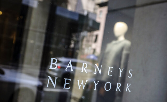 FILE - In this July 16, 2019, file photo signage for Barneys New York department store is displayed on the store's window in New York. Luxury chain Barneys New York has penned a deal to sell its assets for $271.4 million to Authentic Brands Group, a licensing company that owns such brands as Nine West and Aeropostale, and investment bank B. Riley Financial Inc., according to court documents filed late Wednesday, Oct. 16. (AP Photo/Bebeto Matthews, File)