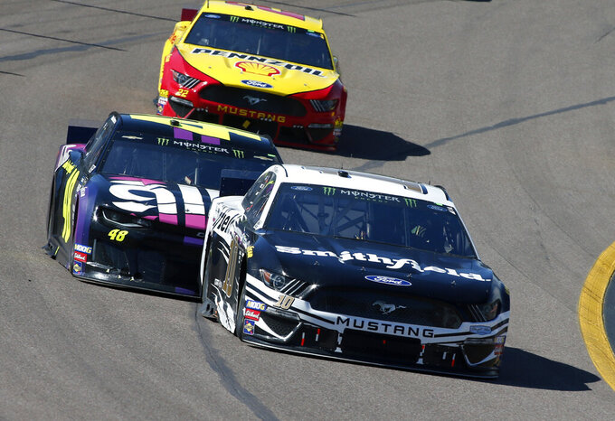 Aric Almirola (10) leads Jimmie Johnson (48) and Joey Logano (22) out of Turn 4 during the NASCAR Cup Series auto race at ISM Raceway, Sunday, March 10, 2019, in Avondale, Ariz. (AP Photo/Ralph Freso)