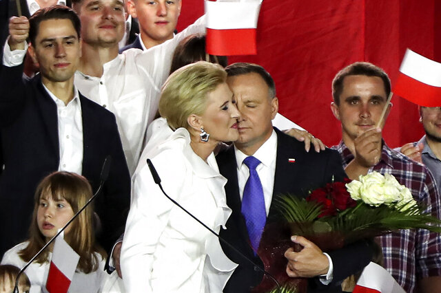 Incumbent President Andrzej Duda is hugged by his wife Agata Kornhauser-Duda in Pultusk, Poland, Sunday, July 12, 2020. An exit poll in Poland's presidential runoff election shows a tight race that is too close to call between the conservative incumbent, Andrzej Duda, and the liberal Warsaw mayor, Rafal Trzaskowski.(AP Photo/Czarek Sokolowski)