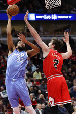 Minnesota Timberwolves center Karl-Anthony Towns, left, shoots against Chicago Bulls forward Luke Kornet during the first half of an NBA basketball game in Chicago, Wednesday, Jan. 22, 2020. (AP Photo/Nam Y. Huh)