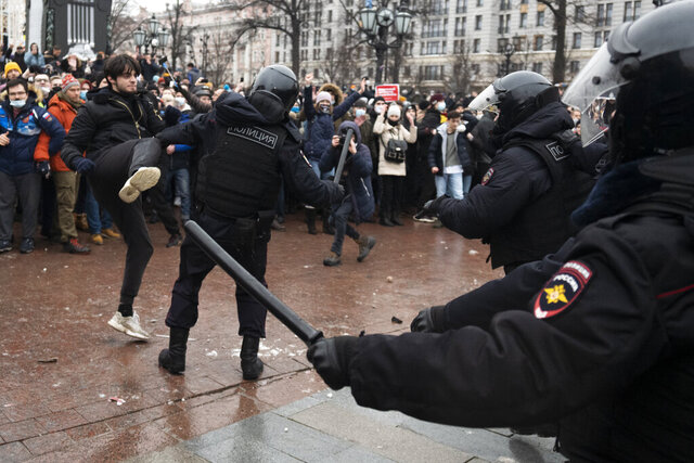 A demonstrator clashes with a police officer during a protest against the jailing of opposition leader Alexei Navalny in Pushkin square in Moscow, Russia, Saturday, Jan. 23, 2021. Russian police arrested more than 3,400 people Saturday in nationwide protests demanding the release of opposition leader Alexei Navalny, the Kremlin's most prominent foe, according to a group that counts political detentions. In Moscow, an estimated 15,000 demonstrators gathered in and around Pushkin Square in the city center, where clashes with police broke out and demonstrators were roughly dragged off by helmeted riot officers to police buses and detention trucks. Some were beaten with batons. (AP Photo/Victor Berezkin)