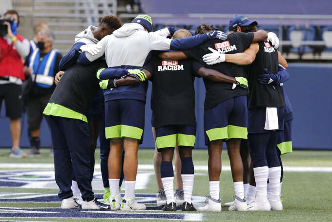 Seattle Seahawks players huddle while wearing t-shirts in support of Black Lives Matter before an NFL football game against the New England Patriots, Sunday, Sept. 20, 2020, in Seattle. (AP Photo/John Froschauer)