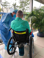 """In this photo provided by Cho Ray Hospital, a doctor attends to """"Patient 91"""", a British pilot who survived COVID-19 and seated on a wheelchair as he was recovering at Cho Ray hospital on June 11, 2020 in Ho Chi Minh City, Vietnam.  The British pilot who was Vietnam's most critical COVID-19 patient is virus free and has recovered enough to make the long flight home next Sunday, doctors said, Monday, July 6. (Cho Ray Hospital via AP)"""