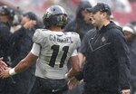 Central Florida coach Josh Heupel and quarterback Dillon Gabriel (11) celebrate in the rain after a touchdown against Marshall during the Gasparilla Bowl NCAA college football game Monday, Dec. 23, 2019, in Tampa, Fla. (Stephen M. Dowell/Orlando Sentinel via AP)