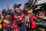 Driver Carlos Sainz, of Spain, center, is congratulated by Driver Stephane Peterhansel, of France, left, and driver Nasser Al-Attiyah, of Qatar, right, at the end of stage twelve of the Dakar Rally between Haradth and Qiddiya, Saudi Arabia, Friday, Jan. 17, 2020. (AP Photo/Bernat Armangue)