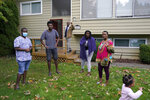 Sophonie Bizimana, center, a permanent U.S. resident who is a refugee from Congo, waves from the steps of his home in Kirkland, Wash., Wednesday, Oct. 14, 2020, as four of his children and a granddaughter look on. Bizimana's wife, Ziporah Nyirahimbya, is in Uganda and has been unable so far to join him in the U.S. For decades, America admitted more refugees annually than all other countries combined, but that reputation has eroded during Donald Trump's presidency as he cut the number of refugees allowed in by more than 80 percent. (AP Photo/Ted S. Warren)