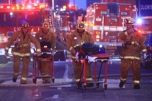Los Angeles Fire Department firefighters push ambulance cots at the scene of a structure fire that injured multiple firefighters, according to a fire department spokesman, Saturday, May 16, 2020, in Los Angeles. (AP Photo/Damian Dovarganes)