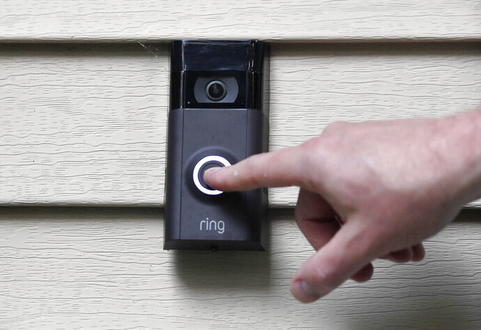 "FILE - In this July 16, 2019, file photo, Ernie Field pushes the doorbell on his Ring doorbell camera at his home in Wolcott, Conn. Amazon says it has considered adding facial recognition technology to its Ring doorbell cameras. The company said in a letter released Tuesday, Nov. 19 by U.S. Sen. Ed Markey that facial recognition is a ""contemplated, but unreleased feature"" of its home security cameras. The Massachusetts Democrat wrote to Amazon CEO Jeff Bezos in September raising privacy and civil liberty concerns about Ring's video-sharing partnerships with hundreds of police departments around the country.   (AP Photo/Jessica Hill, File)"