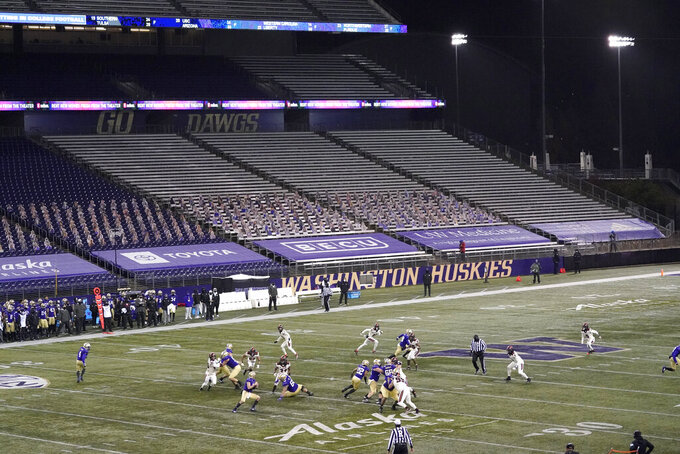 FILE - In this Nov. 14, 2020, file photo, Washington quarterback Dylan Morris drops to pass against Oregon State in front of empty seats at Husky Stadium during the second half of an NCAA college football game in Seattle. Washington begins the 2021 season as one of the favorites in the Pac-12 North Division, while also trying to erase the bad taste of how last year ended when a COVID-19 outbreak brought a sudden end to an already truncated schedule. (AP Photo/Ted S. Warren, File)