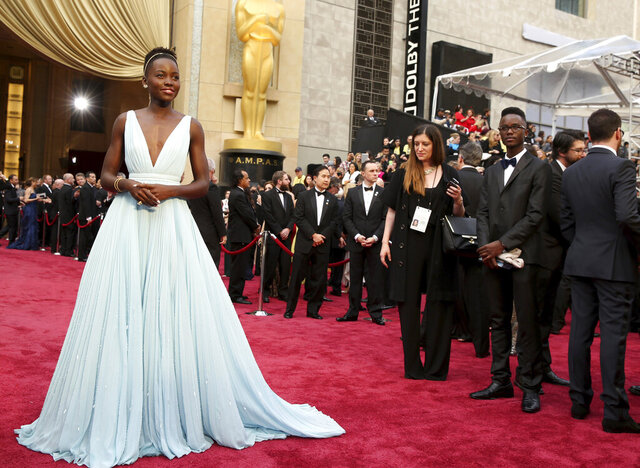 FILE - This March 2, 2014 file photo shows Lupita Nyong'o in a pale blue Prada dress at the Oscars in Los Angeles. What happens to the duds after a big awards night can be a peculiar affair that depends on the relationship a celebrity has with a designer. Nyong'o, who won the Oscar for best supporting actress for