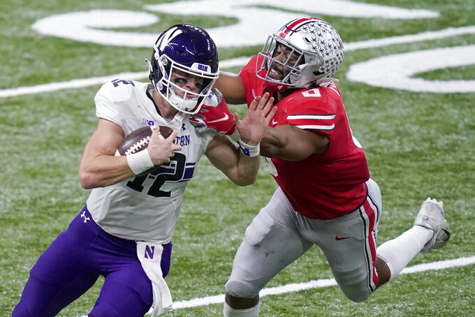 Northwestern quarterback Peyton Ramsey (12) runs with the ball as Ohio State defensive end Jonathon Cooper defends during the second half of the Big Ten championship NCAA college football game, Saturday, Dec. 19, 2020, in Indianapolis. (AP Photo/Darron Cummings)