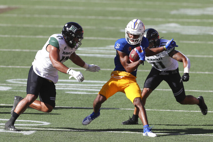 San Jose State wide receiver Tre Walker (10) tries to avoid Hawaii linebacker Isaiah Tufaga (17) and defensive back Sterlin Ortiz (11) during the second half of an NCAA college football game Saturday, Dec. 5, 2020, in Honolulu. (AP Photo/Marco Garcia)