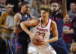 Massachusetts' Tre Mitchell, center, is pressured by Dayton's Obi Toppin, left, and Trey Landers, right, in the first half of an NCAA college basketball game, Saturday, Feb. 15, 2020, in Amherst, Mass. (AP Photo/Jessica Hill)