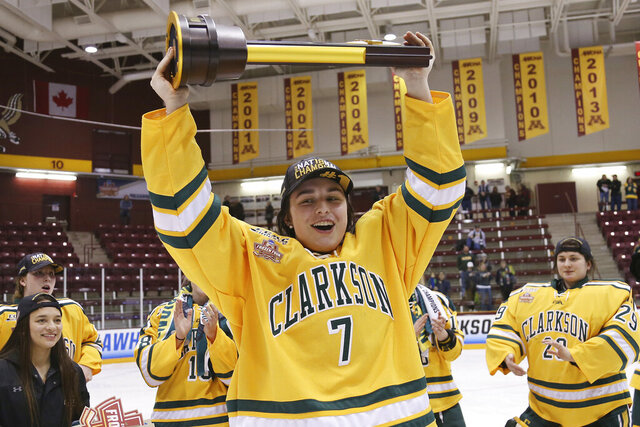 FILE - In this March 18, 2018, file photo, Clarkson's Elizabeth Giguere (7) holds up the trophy after they defeated Colgate 2-1 in overtime in the NCAA college women's hockey Frozen Four championship game in Minneapolis. The junior forward has been selected as the Patty Kazmaier Memorial Award winner, announced Friday, March 27, 2020. It's presented annually to the most outstanding player in women's college hockey. (AP Photo/Stacy Bengs, File)