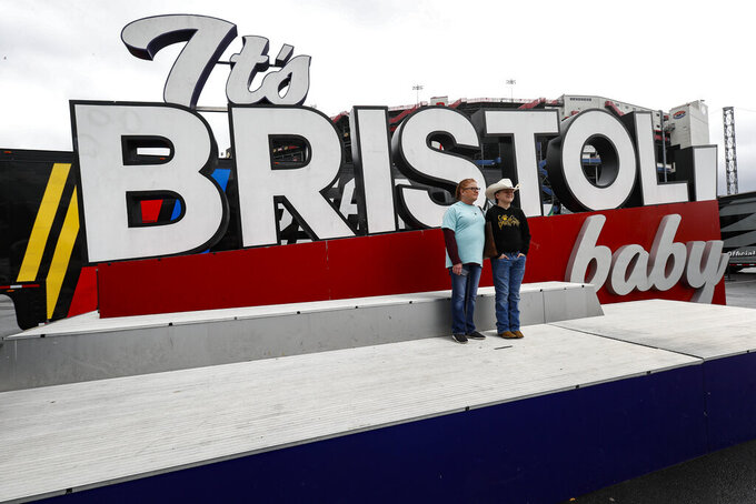 """Lisa Odle and Elijah Duke of Nashville, Tenn. have their photo taken in front of the """"It's BRISTOL baby"""" sign after races for both the Truck Series and NASCAR Cup Series auto race was postponed due to inclement weather at Bristol Motor Speedway, Sunday, March 28, 2021, in Bristol, Tenn. (AP Photo/Wade Payne)"""