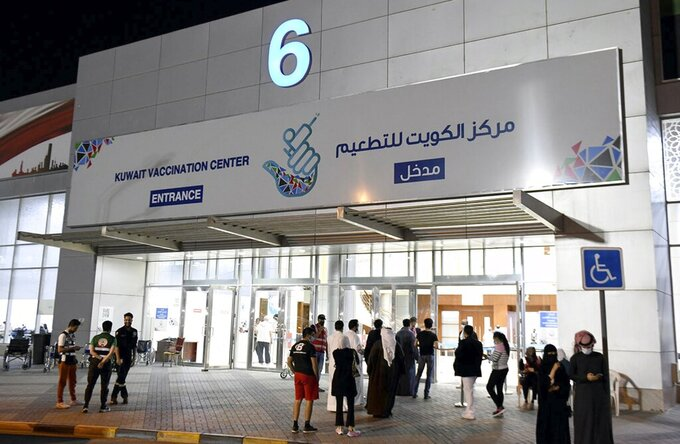 In this Friday, March 12, 2021 photo released by Kuwait News Agency, KUNA, people enter Kuwait Vaccination Centre to get the vaccine in Kuwait. In the tiny, oil-rich sheikhdom of Kuwait, the foreigners who power the country's economy, serve its society and make up 70% of its population are struggling to get COVID-19 vaccines. (KUNA via AP)